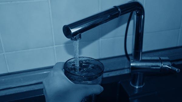 Eine Hand hält ein Glas unter einen laufenden Wasserhahn